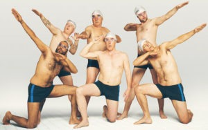 Six men in swimming trunks pose